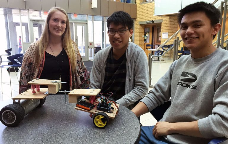Second-year School of Engineering students Kaitie, Darryl, and Peter put the finishing touches on their Mars Lander that will be tested at the year-end competition Friday morning.