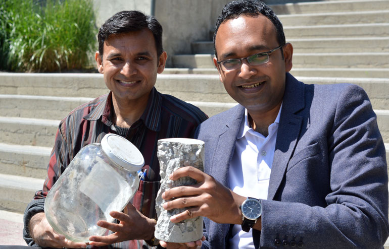 UBC's Anant Parghi (left) and Shahria Alam hold up a piece of 'green' concrete and some of the glass that helped make it.