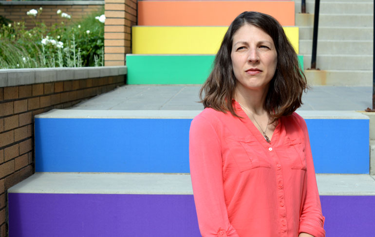 Susan Holtzman stands in front of the 'rainbow staircase' of inclusion at UBC's Okanagan campus.