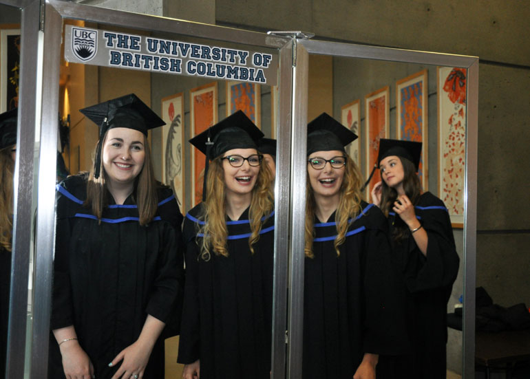 Lauren Vander Molen and Amy Morey share a laugh in the mirror as they prepare for UBC's convocation