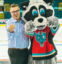 HatTrick participant Kevin Lavigne and poses with Kelowna Rockets mascot Rocky the Raccoon.