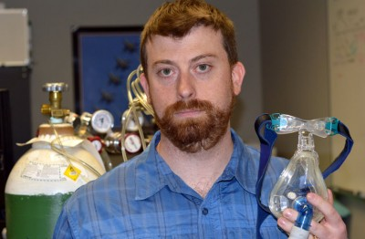 UBC's Glen Foster, seen holding breathing apparatus in his lab, is researching the health impacts of sleep apnea.