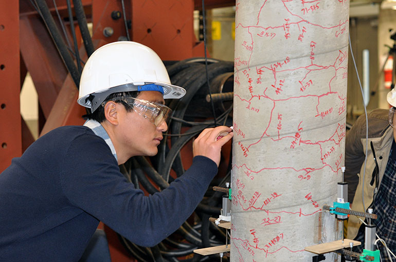 Student Peng Zhang traces cracks in the column during a strength test in UBC Okanagan's Applied Laboratory for Advanced Materials and Structures.
