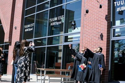Graduates throw their mortarboards into the air to celebrate their success after receiving their degrees.