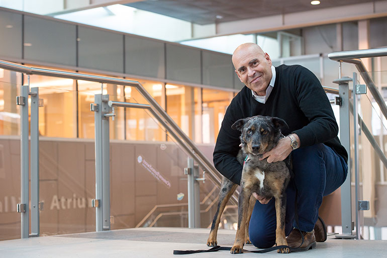 Education professor John-Tyler Binfet poses with Frances. The pair has offered a drop-in animal-assisted therapy program at UBC Okanagan for five years.