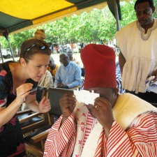 UBC Faculty of Education's Carly Bokor shows Paramount Chief of the Nabdam Region how to use the Foldscope.