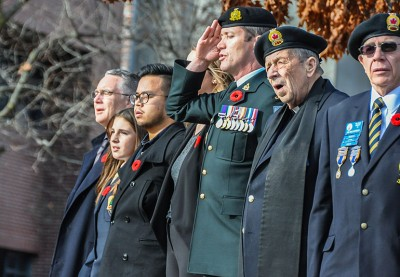 Lieutenant-Colonel Mike McGinty, centre, salutes while participants at UBC Okanagan's 2016 Remembrance Day service sing O'Canada.
