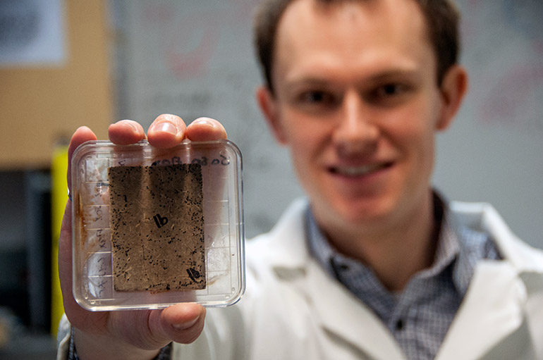 UBC researcher Bryn Crawford holds a sample sheet made with flax bio-waste. The black spots on the sheet indicate mould growth.