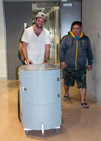 Metro Community Church representatives Devon Siebenga and Ramsay Collier push the prototype personal belonging carrier out of the lab at UBC Okanagan's Composites Research Network lab.