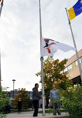 UBC students Briana Wilson and Cody Isaac raise the Syilx Okanagan Nation flag during a special ceremony at UBC's Okanagan campus.