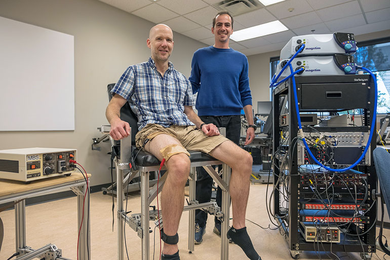 UBC Assist. Prof. Chris McNeil and doctoral student Luca Ruggiero test leg fatigue using a specialized device called an isometric dynamometer.