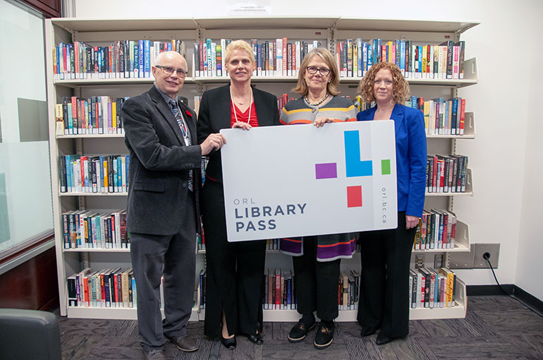 Don Nettleton, far left, and Monica Gaucher, both with the Okanagan Regional Library, present UBC Okanagan's Deborah Buszard her own library card. Also pictured is UBC Okanagan Chief Librarian Heather Berringer.