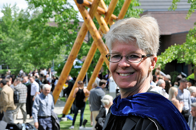 Nursing Professor Kathy Rush overlooks the courtyard as nursing students mingle after their graduation at UBCO.