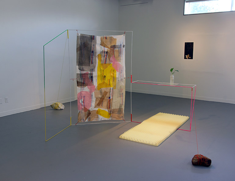 Carmen Winther's installation of her untitled artwork uses room dividers and food storage containers.