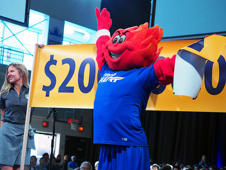 UBCO Heat mascot Scorch waves to the crowd as President Santa Ono announces the Blue & Gold campaign target has been raised to $200,000,000.