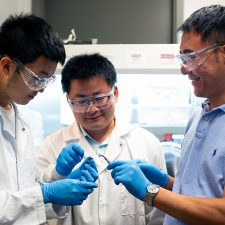 UBCO engineering students Peter Zhao and Huibing He examine the component of a tiny lithium-tellurium battery along with assistant professor Jian Liu (right).