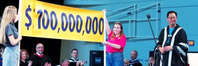 UBCO students Catherine Fleck-Vidal and Mykela White hold up a banner as President Santa Ono announces the $100,000,000 fundraising campaign has been met a year earlier than planned.