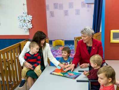 UBCO Professor Lesley Lutes, president of the Learning Centre's board of directors, (left) holds Eli while she reads a story with Katrine Conroy, Minister of Children and Family Development to Lucas, Tyler and Amelia.