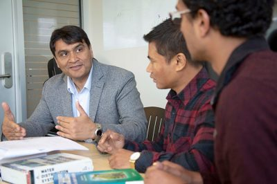 UBC Okanagan's Rehan Sadiq, left, discusses drinking water assessment tools and benchmarking strategies with students Gyan K C Shrestha and Sarin Raj Pokhrel.