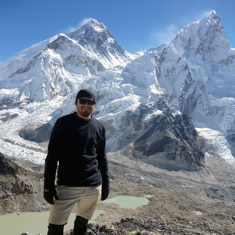 UBC Okanagan's Governor General gold medal winner Mike Tymko stands at a landmark called Kala Patthar with Mount Everest in the background.