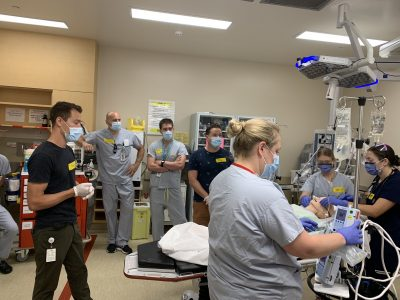 Simulation session in the KGH emergency department. Note: in order to conserve PPE, the team pictured here is not wearing PPE appropriate for simulation but not bedside patient care.