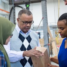 UBCO Engineering Professor Solomon Tesfamariam (centre) examines wood used in mass-timber buildings.