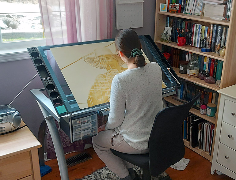 BFA student Stephanie Tennert works in her home studio on a drawing in preparation for the year end exhibition.