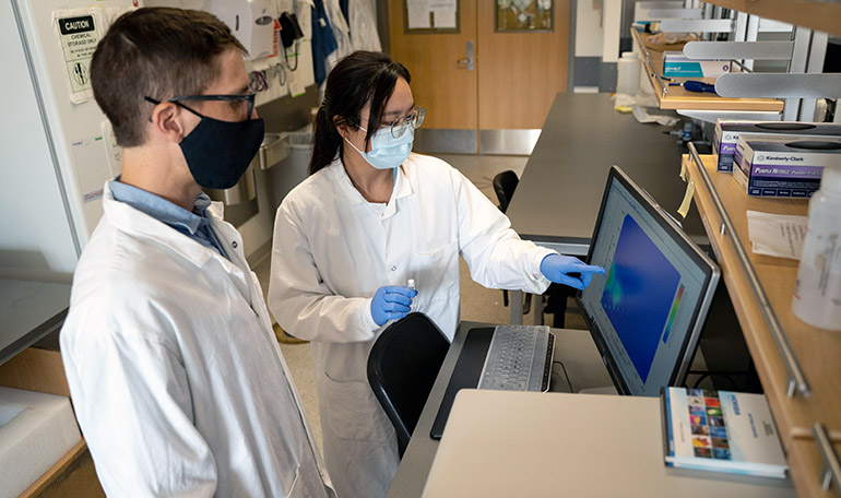 UBC researchers Nicolas Peleato and Li Ziyu examine the data after testing a water sample with a florescence spectrometer.