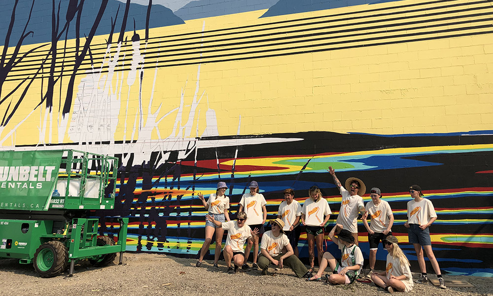 Students and faculty pose in front of new mural in downtown Kelowna