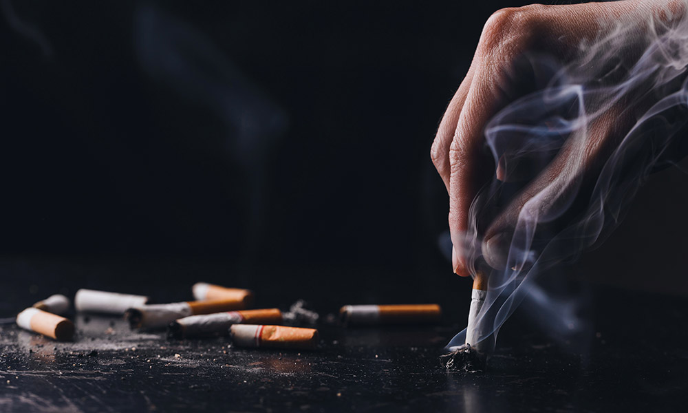 photo of a hand stubbing out a cigarette
