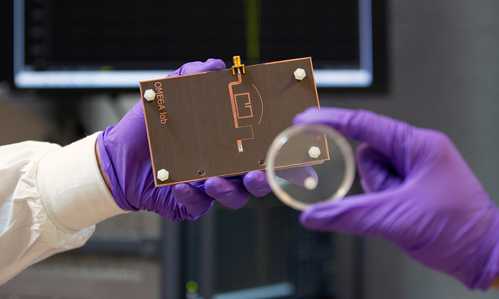 Lab technicians holding up portable and reusable microwave sensor
