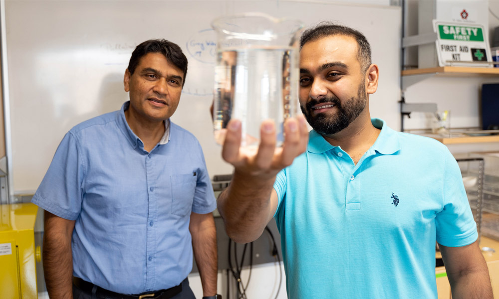 two researchers holding up a glass of water