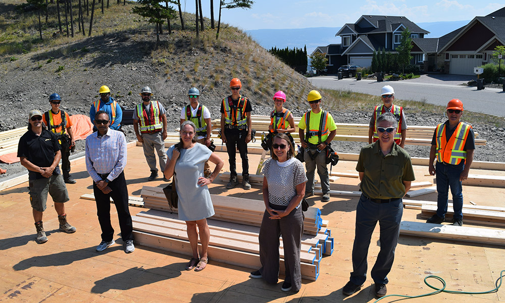(L to R) (front row): Dom Caron, Authentech Homes; Dr. Shahria Alam, UBC School of Engineering, Karin Eger-Blenk, Wilden; Carol Suhan, Fortis BC; Dr. Andrew Hay, Okanagan College; (back row): Okanagan College carpentry students with instructor Tim Dorn (second from right) and Stephen Speers, Dean of Trades and Apprenticeship (right).