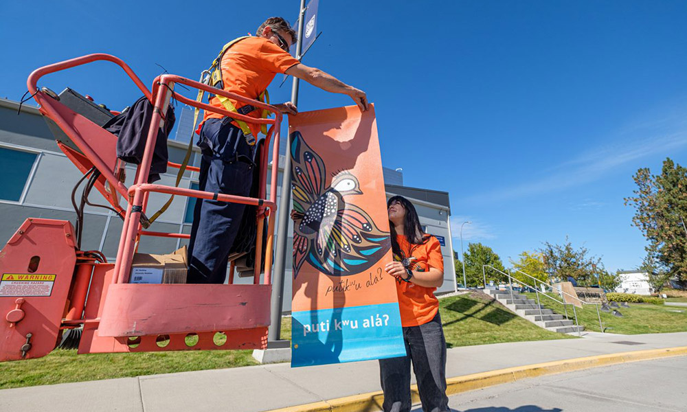 A student passing an Orange Shirt Day Banner to a UBCO employee